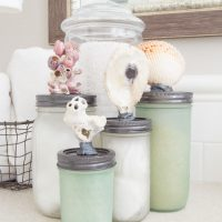 Beachy AND functional! Make this sea glass mason jar storage with just some simple spraypaint and shells from your collection! www.tableandhearth.com