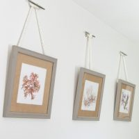 Such a pretty way to hang pictures! DIY Nautical Rope Picture Hangers