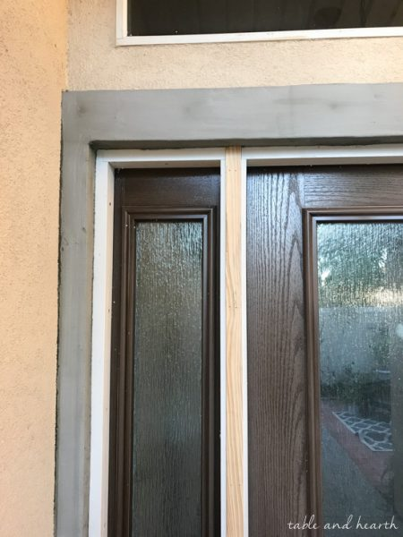 Installing a new entry door unit on a stucco home can be a daunting project. See how it went for this blogger's crew as they installed a beautiful new unit on a mid-90s stucco home! #thermatrudoors #entrydoor #wooddoor #fiberglassdoor www.tableandhearth.com