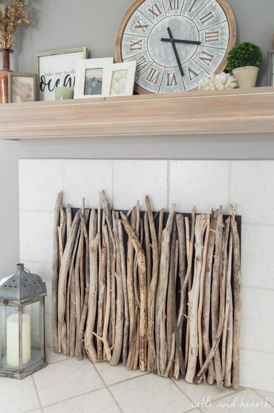 Beautiful! Cover your fireplace with coastal style with this Driftwood DIY Fireplace Cover! #fireplace #fireplacecover #driftwood